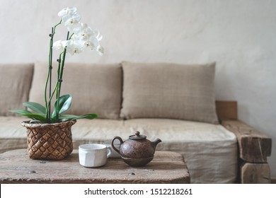 Enfoque selectivo de tetera de arcilla, taza blanca y flor de orquídea en la mesa de madera contra la pared borrosa con espacio de copia en el fondo. Acogedora casa con cómodo sofá en estilo interior vintage