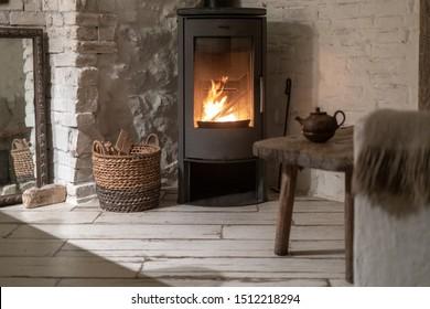 Rieten mand met brandhout dichtbij brandschoorsteen. Houtkachel open haard met metalen behuizing en glazen deur in comfort huis met gezellig interieur op kamer