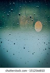 背景に暗い雨雲とガラス板上の雨滴