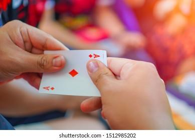 Schließen Sie oben von Mannhand, die Spielkarte auf einem unscharfen Hintergrund hält, Ass der Diamanten und König dahinter.