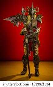 Herečka žena v maske a kostýme postavy fiktívnej fantázie pózuje na červenom pozadí