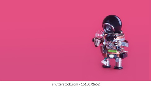 Machine learning and creative idea concept. Funny robotic toy holds light bulb. creative design futuristic robot on pink background. copy space for advertising text.