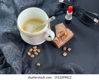 Cappuccino in a white cup red lipstick. Glasses, cosmetics for the lips. Black fabric, lace. Milk chocolate. Coffee beans brown.