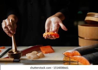 Primer de las manos del cocinero que preparan la comida japonesa. Chef japonés haciendo sushi en el restaurante. Joven chef haciendo sushi japonés tradicional en tabla de cortar.