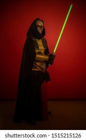 Schauspieler ein Mann in einer Maske und in Kostümen von fiktiven Fantasy-Figuren, die auf einem roten Hintergrund posieren