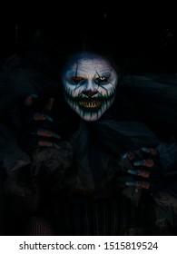 Hellga Scary Clown escondido debajo del tren oscuro con las manos saliendo