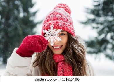 concepto de personas, temporada y Navidad - retrato de feliz sonriente adolescente o mujer joven con copo de nieve en Winter Park