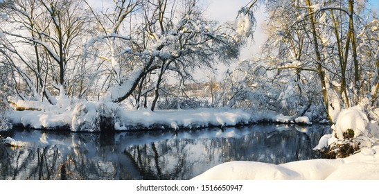 Frosty winter scene with flowing forest river on a sunny morning and beautiful snow covered trees in the glow of rising sun.