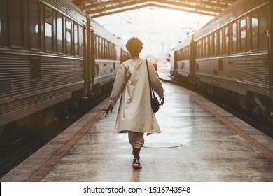 鉄道駅の屋内のプラットフォームで出発を待っている2つの高速道路列車の間の彼女の旅行の前に鉄道駅の白いマントで歩いているアフリカの女性の背面図