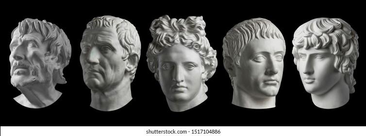 Cinco copias de yeso de antiguas cabezas de estatua aisladas sobre fondo negro. Escultura de yeso mans caras.