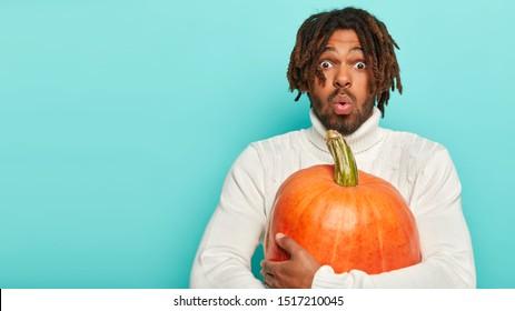 Foto de asombrado hombre negro sostiene una gran calabaza naranja, asustado por algo, tiene un peinado específico, sorprendido con una rica cosecha estacional, viste un suéter blanco. Concepto de preparación de personas y Halloween