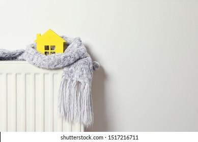 Huismodel verpakt in sjaal op radiator binnenshuis, ruimte voor tekst. Efficiëntie van verwarming in de winter