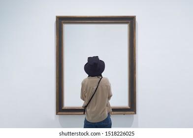 Vista interior de una niña solitaria o un turista mirando un lienzo en blanco o una pintura en un museo o galería
