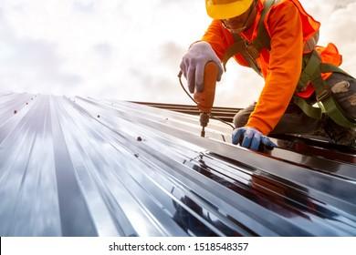建設作業員は、新しい屋根、屋根ふきツール、金属シートを使用して新しい屋根に使用される電気ドリルを設置します。