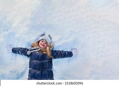 Mooi klein meisje dat Marine jasje en gebreide muts draagt die in een besneeuwde winterpark spelen. Kind spelen met sneeuw in de winter. Kinderen spelen en springen in het besneeuwde bos. Familievakantie met kind in de bergen