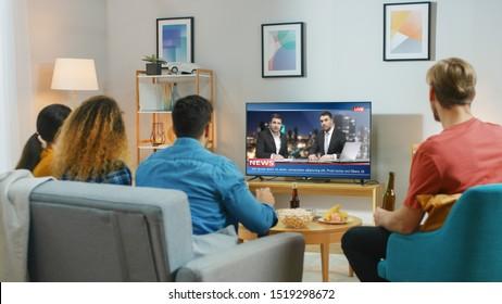Amigos felices sentados en casa viendo noticias. Relajarse en un acogedor apartamento de Couch.right con amigos comiendo bocadillos y divirtiéndose.