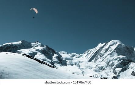 Wunderschöner schneebedeckter Bergblick mit Gleitschirm. Paragliding in der Schweizer Alpenregion Matterhorn, Schweiz. Konzept des Extremsports, Abenteuer / Herausforderung annehmen.