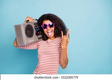 Foto de elegante, alegre, lindo, agradable, ventilador de heavy metal que sobresale que le muestra los dedos de la señal de rockero con cuernos sosteniendo la grabadora de radio con una camiseta a rayas aislada sobre fondo de color azul pastel