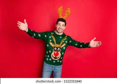 Portrait of excited funky funny man feel crazy hold hands invite on his cool event christmas theme party wear deer reindeer seasonal pattern sweater isolated over red color background