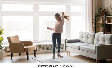 Feliz joven despreocupada bailando sola divirtiéndose en casa escuchando buena música, enérgica chica moviéndose saltando en el interior de la moderna sala de estar con ventana grande disfruta de libertad y estilo de vida activo