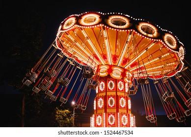 Carrusel de cadena oscilante iluminado en el parque de atracciones por la noche