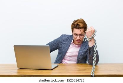 チェーンで彼の机で働く若い赤毛の実業家