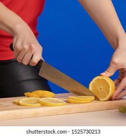 Emotionales junges Mädchen hält Obst und Gemüse in ihren Händen, verwöhnt und posiert auf einem blauen Hintergrund