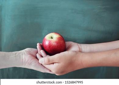 黒板の背景、幸せな先生の日、健康、寄付の概念を持つ赤いリンゴを保持している学生と教師の手