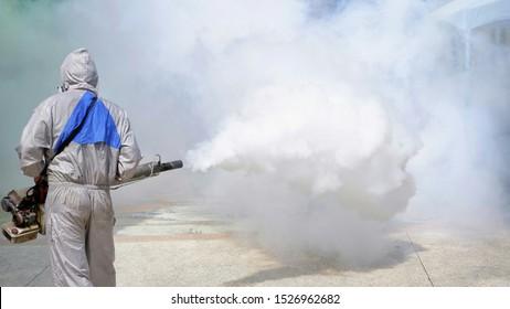 Vista trasera del trabajador de la salud al aire libre con ropa protectora que usa una máquina nebulizadora que rocía productos químicos para eliminar los mosquitos y prevenir el dengue en una ubicación general en la comunidad