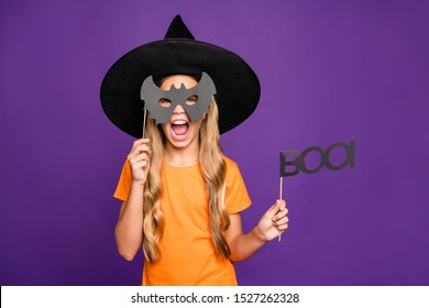 Grr! Photo of little witch lady play paranormal role halloween theme party holding bat paper stick scary look wear orange t-shirt wizard hat isolated purple color background