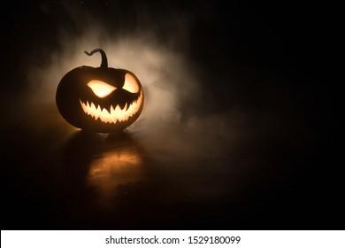 Sonrisa de calabaza de Halloween y ojos aterradores para la noche de fiesta. Vista de cerca de la aterradora calabaza de Halloween con los ojos brillando en el interior en fondo negro. Enfoque selectivo