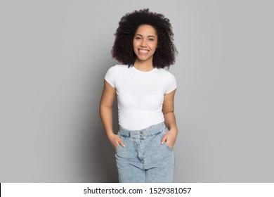 灰色のスタジオの背景に分離されたカジュアルな服を着た幸せなアフリカ系アメリカ人の若い女性ポーズ、笑顔の混血民族ミレニアル世代の女の子モデルまたは女優がジーンズで手をつなぐ