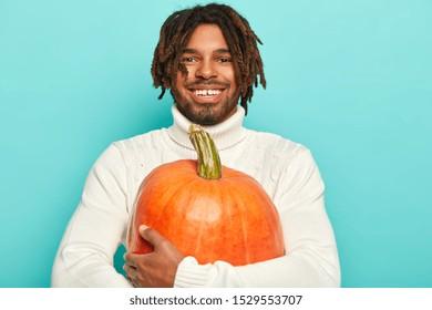 El retrato del chico sonriente feliz tiene un estado de ánimo feliz, lleva una calabaza naranja grande, lista para cocinar un plato de verduras de productos orgánicos, viste un suéter blanco, aislado sobre fondo azul. Concepto de tiempo de otoño