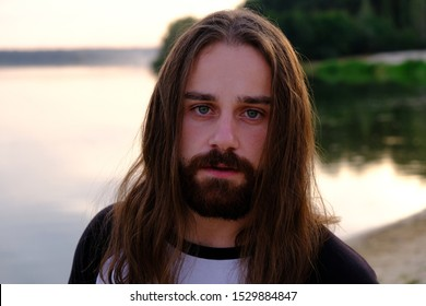 クローズアップ、夕日の川のカメラで芸術的に見える長い流れる髪を持つハンサムな白人のひげを生やした若い男の肖像画。