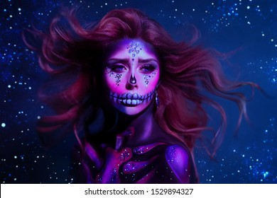 Portrait charming young woman with cute pink face red hair flying from wind poses in the purple neon light, image of skeleton using body art, dead princess. Celebrate Dia de los Muertos. Parade legend