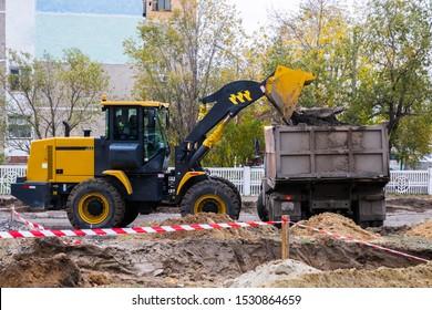 Der Lader lädt die Erde in einen Muldenkipper auf der Baustelle.