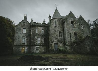 Espeluznante castillo abandonado en Escocia ubicado en el verde follaje de invierno. Los campanarios de los castillos se contraponen a un fondo de cielo gris oscuro. La escena es espeluznante, espeluznante, solitaria y fría.