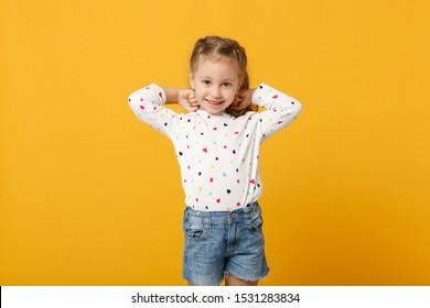 Kleines niedliches Kindkindbaby 4-5 Jahre alt, das leichte Denimkleidung trägt, die auf pastellgelbem Wandhintergrund, Kinderstudioporträt lokalisiert wird. Muttertag, Liebesfamilie, Elternschaftskindheitskonzept