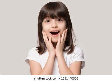Disparo en la cabeza de la pequeña niña en edad preescolar sorprendida, mira a la cámara, se siente aturdida por las buenas noticias inesperadas, niño pequeño feliz aislado en el fondo gris del estudio sorprendido por una sorpresa increíble