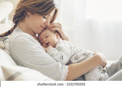 Liefhebbende moeder die thuis haar pasgeboren baby draagt. Helder portret van gelukkige moeder slapende baby kind op handen te houden. Moeder knuffelen haar zoontje van 2 maanden.