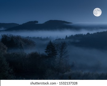 The chilling scenery of forested hills in fog with the full moon in the blue sky at night time - werewolves horror twilight concept