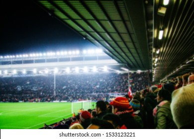Blurred background of football players playing and soccer fans in match day on beautiful green field with sport light at the stadium. Sports,Athlete,People Concept.Mercy Side,Anfield,Liverpool.UK