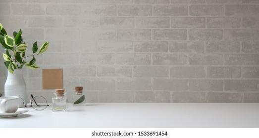 Minimaler Arbeitsbereich mit Kopierraum und Büromaterial auf weißem Schreibtisch und grauem Backsteinmauerhintergrund