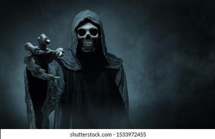 コピースペースのある暗い背景の上でカメラに向かって手を伸ばす死神