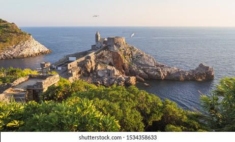 Impresionante puesta de sol en el Golfo de los Poetas. Hermoso paisaje de Porto Venere en Italia. Ruinas del castillo de Doria, iglesia de San Pedro en un acantilado, pequeña isla de Palmaria, mar Mediterráneo y gaviotas.