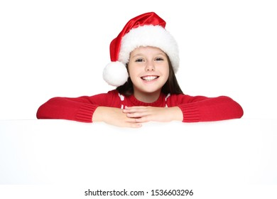 Little girl in christmas sweater and hat with blank board on white background