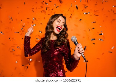 Portrait of charming pop start girl have karaoke party on her prom sing song hold microphone enjoy loud music wear maroon outfit isolated over orange color background confetti falling