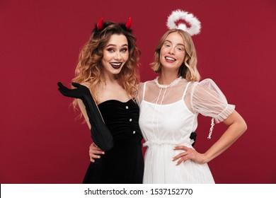 Bild eines glücklichen positiven Frauenengels und -dämons in Karnevalskostümen lokalisiert über rotem Wandhintergrund.