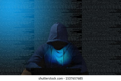 Hacker at the table with a laptop on the background of source code.  Darknet.  Deepweb.