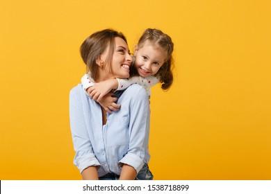 Vrouw in lichte kleren veel plezier met schattig kind babymeisje 4-5 jaar oud. Mama kleine jongen dochter geïsoleerd op gele achtergrond studio portret. Moederdag liefde familie ouderschap jeugd concept